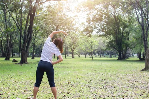 Junge weibliche übung im park am morgen, frauentraining und entspannen sich vor dem eignungstraining