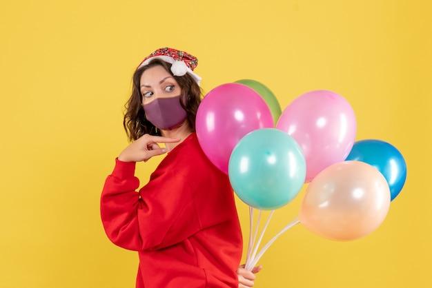Junge weibliche versteckballons der vorderansicht in der sterilen maske auf einer gelben hintergrundfarbfeiertagsemotion neujahrsweihnachtsfrau