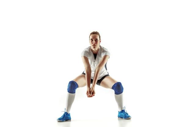 Junge weibliche volleyballspielerin lokalisiert auf weißem studiohintergrund. frau in sportausrüstung und schuhen oder turnschuhen, die trainieren und üben. konzept von sport, gesundem lebensstil, bewegung und bewegung.