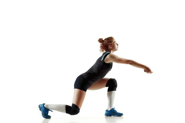 Junge weibliche volleyballspielerin lokalisiert auf weißer wand. frau in sportausrüstung und schuhen oder turnschuhen, die trainieren und üben. konzept von sport, gesundem lebensstil, bewegung und bewegung.