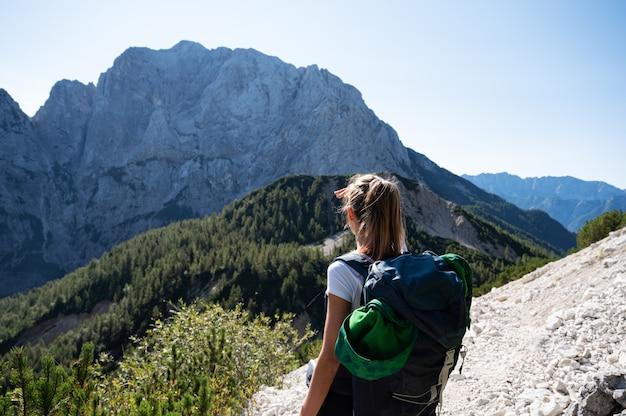 Junge weibliche wandererin mit einem rucksack, der anhält, um die schöne ansicht der berge zu betrachten.