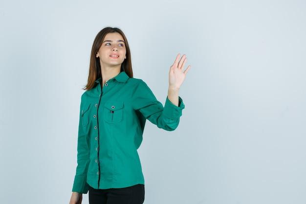 Junge weibliche winkende hand zum begrüßen, während sie im grünen hemd zurückblickt und fröhliche vorderansicht schaut.