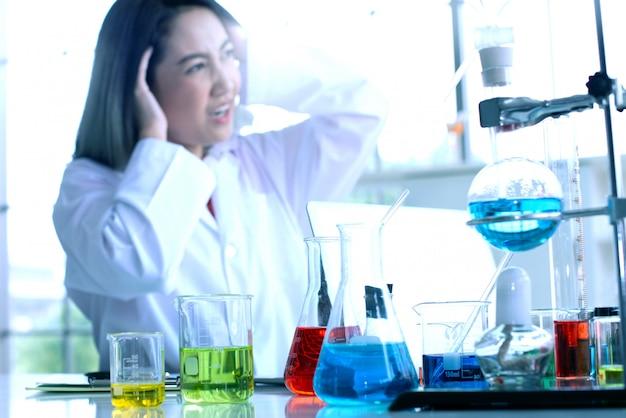 Junge weibliche wissenschaftlerfunktion und gefühl betont im labor, ernste arbeit