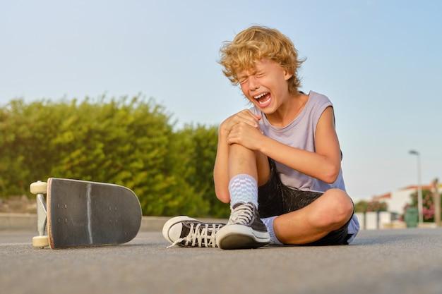 Junge weint, nachdem er in der stadt vom skateboard gefallen ist