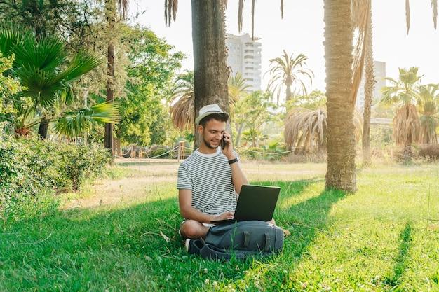 Junge weiße digitale nomaden telefonieren in einem park
