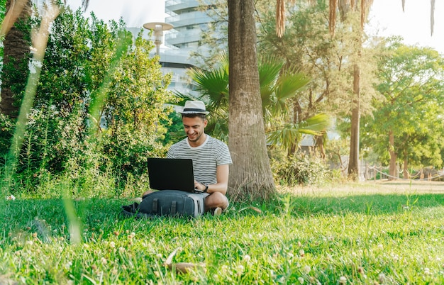 Junge weiße studentin mit einem laptop in einem park