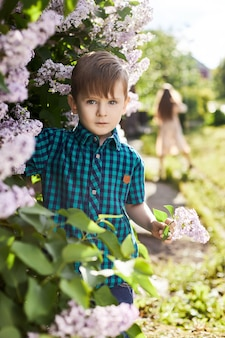 Junge wirft im frühjahr in einem fliederbusch auf. romantisches porträt eines kindes in blumen im sonnenlicht