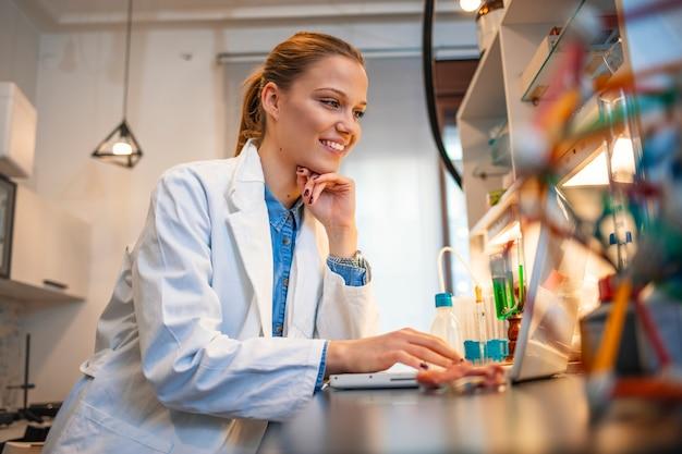 Junge wissenschaftlerin, die am computer in einem labor arbeitet