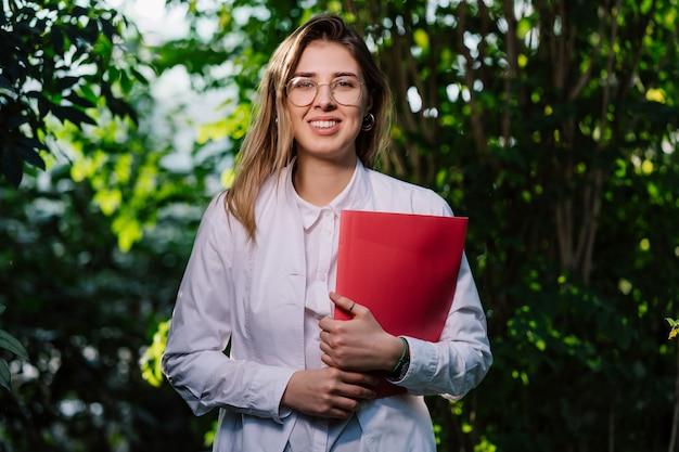 Junge wissenschaftlerin, die mit rotem ordner aufwirft