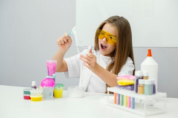 Junge wissenschaftlerin, die mit schleim experimentiert