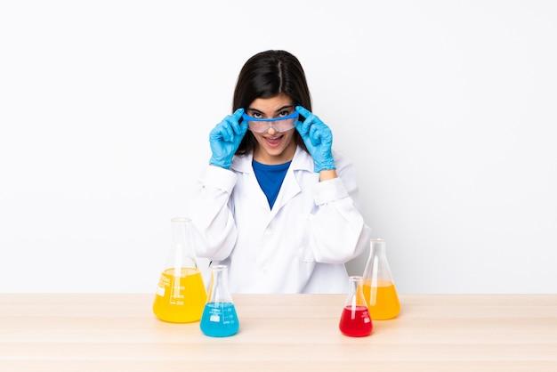 Junge wissenschaftliche frau in einer tabelle mit gläsern und überrascht