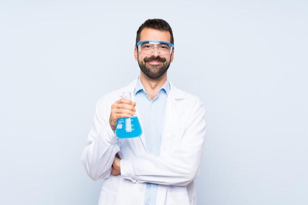 Junge wissenschaftliche haltene laborflasche über der lokalisierten wand, welche die arme gekreuzt in frontaler position hält