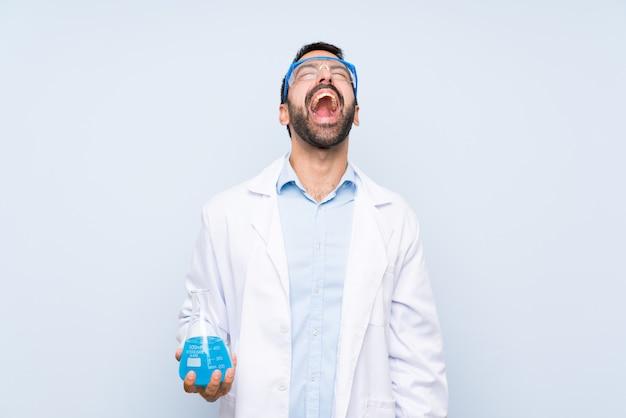Junge wissenschaftliche haltene laborflasche über lokalisiertem hintergrund schreiend zur front mit dem breiten mund öffnen sich