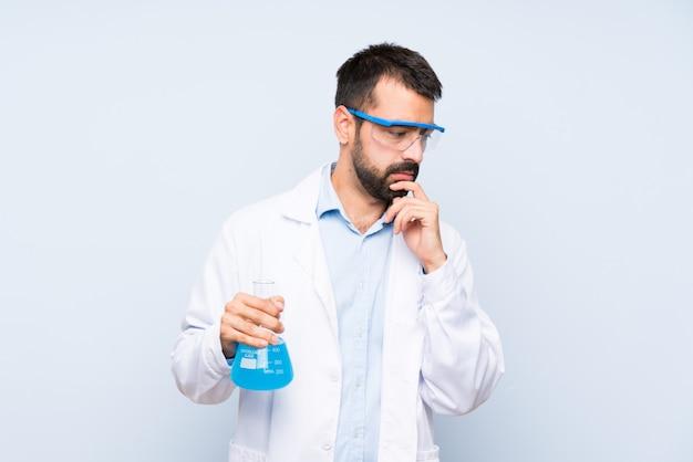 Junge wissenschaftliche haltene laborflasche über lokalisiertem hintergrundbedeckungsmund und schauen zur seite
