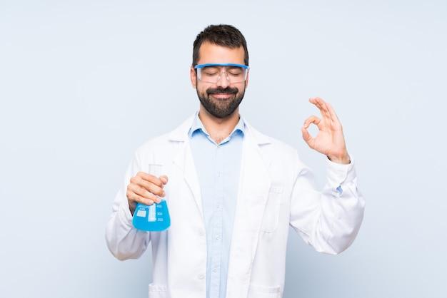 Junge wissenschaftliche haltene laborflasche über lokalisierter wand in der zenhaltung