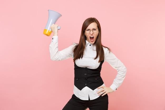 Junge wütende besorgte geschäftsfrau in schwarzem anzug, hemd und brille mit megaphon einzeln auf pastellrosa hintergrund. chefin. erfolgskonzept für karrierevermögen. kopieren sie platz für werbung.