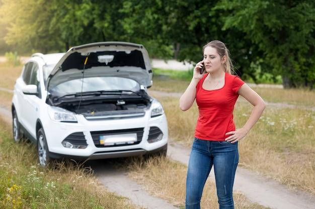 Junge wütende frau, die neben einem kaputten auto auf der wiese um hilfe ruft