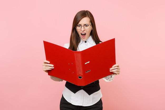 Junge wütende geschäftsfrau mit brille schreit auf der suche nach einem roten ordner nach papierdokumenten einzeln auf pastellrosa hintergrund. chefin. erfolgskonzept für karrierevermögen. kopieren sie platz für werbung.