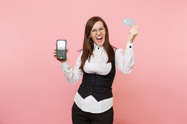 Junge wütende geschäftsfrau schreien halten drahtloses modernes bankzahlungsterminal, um kreditkartenzahlungen zu verarbeiten und zu erwerben, schwarze karte einzeln auf rosafarbenem hintergrund. chefin. erfolg karriere reichtum.
