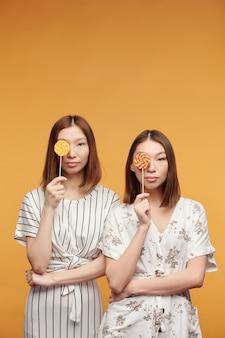 Junge wunderschöne asiatische zwillinge mit lutschern an den augen, die dich ansehen, während sie vor der kamera vor gelbem hintergrund stehen