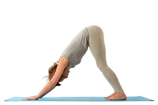 Junge yoga-frau in der adho mukha svanasana (hund) position. auf weißer wand isoliert