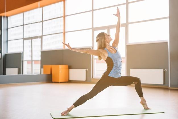 Junge yogafrau, die trainingsübung in der eignungsturnhalle tut