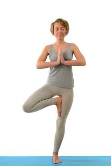 Junge yogafrau in der vrikshasana (baum) position. auf weißer wand isoliert