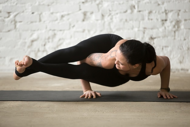 Junge yogi attraktive frau in astavakrasana pose, weiße loft ba