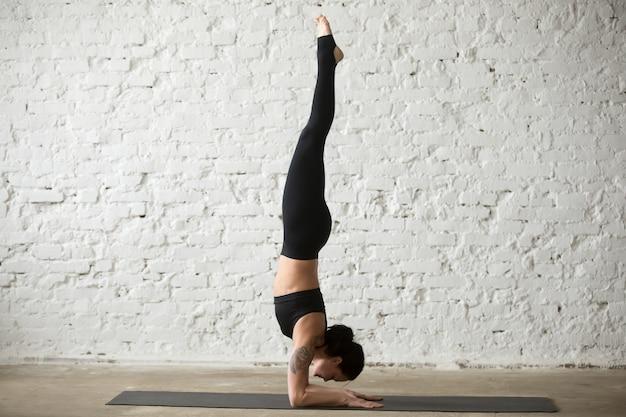 Junge yogi attraktive frau in pincha mayurasana pose, loft zurück
