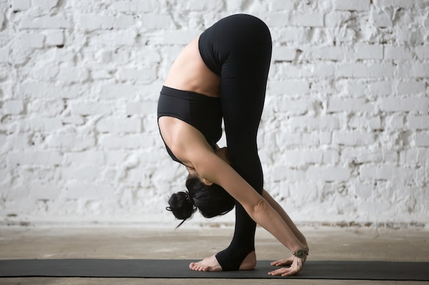 Junge yogi attraktive frau in uttanasana pose, weiße loft backg