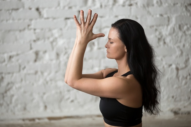 Junge yogi attraktive frau macht namaste, weiße loft backgroun