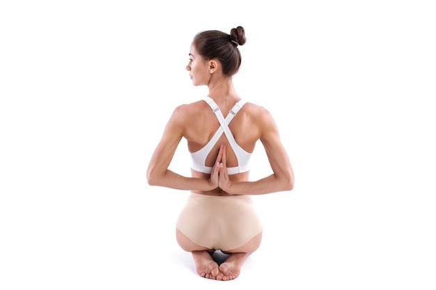 Junge yogifrau, die yoga praktiziert, sitzt in der vajrasana-pose mit namaste hinter dem rücken, in voller länge, rückansicht lokalisiert auf weißem hintergrund. konzept des gesunden lebens.