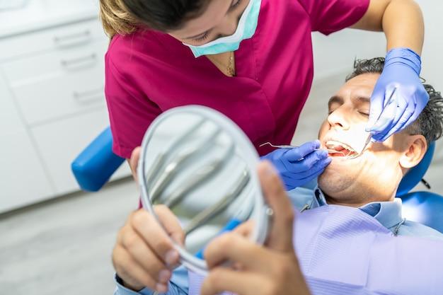 Junge zahnarztfrau, die einen check-up zu einem patienten tut.