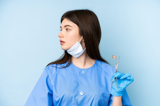 Junge zahnarztfrau, die werkzeuge über der blauen wand schaut seite hält