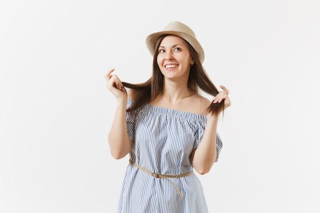 Junge zarte elegante charmante frau gekleidet blaues kleid, süßer hut mit langen brünetten haaren posiert isoliert auf weißem hintergrund. menschen, aufrichtige emotionen, lifestyle-konzept. werbefläche. platz kopieren.