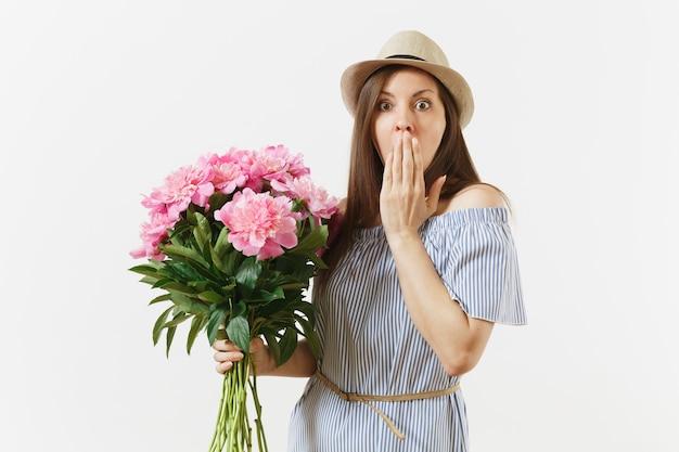Junge zarte frau im blauen kleid, hut, der blumenstrauß der schönen rosa pfingstrosen hält, die auf weißem hintergrund lokalisiert werden. valentinstag, internationaler frauentag-feiertagskonzept. werbefläche.