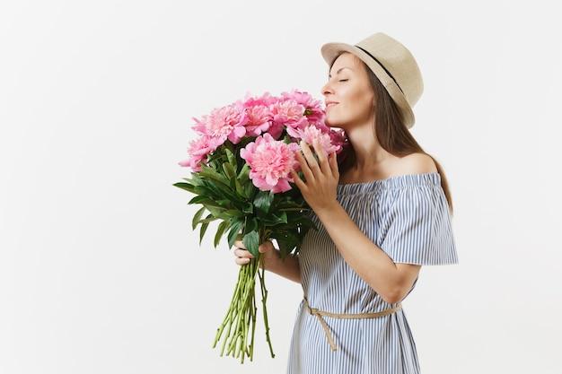 Junge zarte frau im blauen kleid, hut hält, strauß rosa pfingstrosen blumen auf weißem hintergrund schnüffeln. valentinstag, internationaler frauentag-feiertagskonzept. werbefläche.