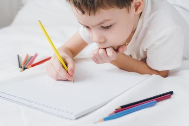 Junge zeichnet mit den bunten bleistiften, die auf dem bett sitzen