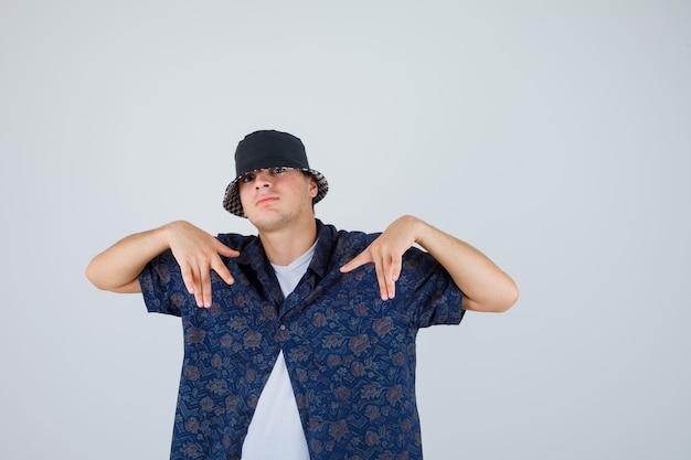 Junge zeigt auf sich selbst mit den händen im weißen t-shirt, im blumenhemd, in der kappe und schaut selbstbewusst, vorderansicht.