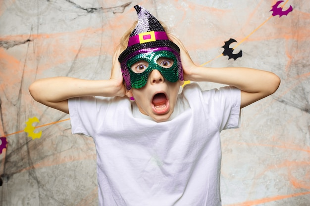 Junge zeigt lustige gesichter für die kamera an halloween Premium Fotos