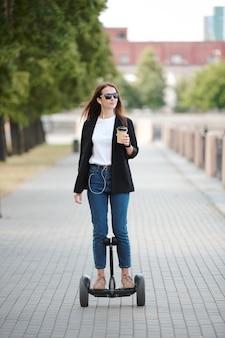 Junge zeitgenössische frau mit einem glas kaffee am flussufer, während sie auf dem gyroskop entlang der straße gegen grüne bäume und gebäude fährt