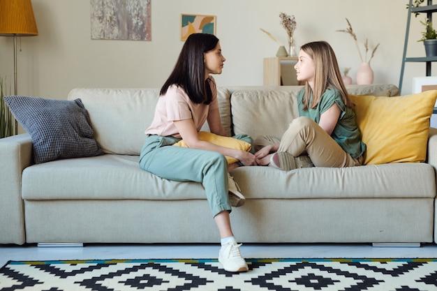 Junge zeitgenössische frau und ihre tochter in freizeitkleidung sitzen sich auf der couch gegenüber, während sie ihre pläne für den tag besprechen