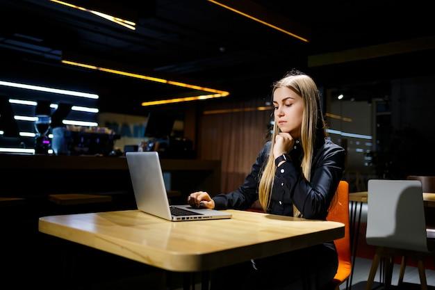 Junge zielgerichtete frau, die an einem neuen geschäftsprojekt im büro arbeitet. bekleidet mit einem schwarzen hemd.