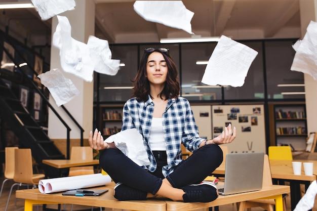 Junge ziemlich freudige brünette frau, die über tischumrandungsarbeitszeug und fliegende papiere meditiert. fröhliche stimmung, pause machen, arbeiten, lernen, entspannen, wahre emotionen.