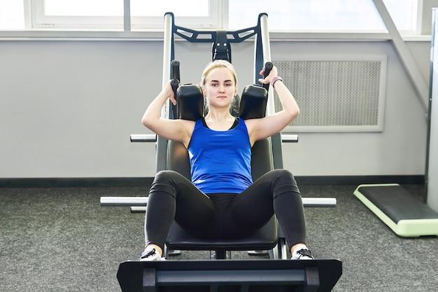 Junge zierliche frau führt kniebeugen mit trainingsgerät im fitnessstudio durch