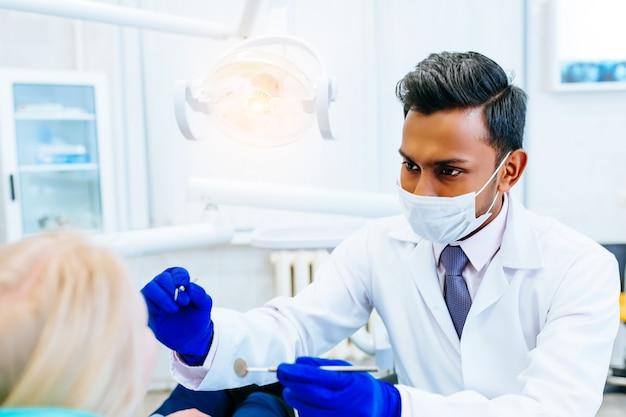 Junge zuversichtlich asiatische männliche zahnarzt ärztliche behandlung für eine patientin in der klinik. zahnklinik-konzept.