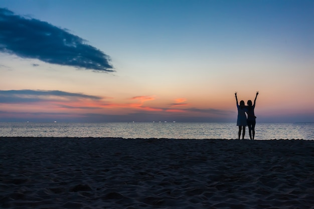 Junge zwei mädchen, die spaß auf dem strand gegen einen hintergrund eines sonnenuntergangs haben
