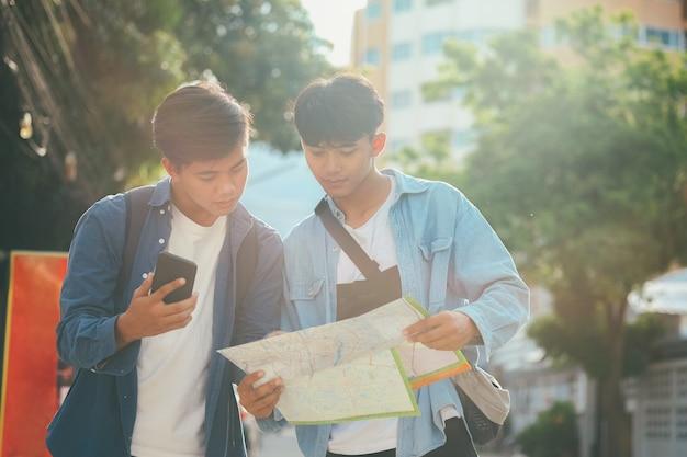 Junge zwei männer reisen zusammen in die stadt in den sommerferien.
