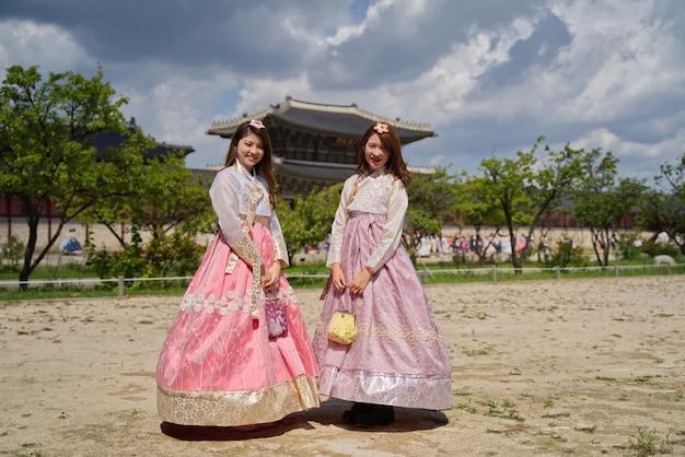 Junge zwei nette asiatische mädchen, die auf traditionelle südkoreanische alte mode hanbok-art ankleiden