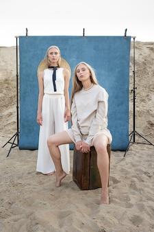 Junge zwillingsmädchen mit langen blonden haaren posieren im sandsteinbruch in eleganter weißer, beiger kleidung